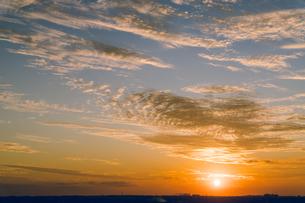 雲を照らす夕日と空一面の夕焼けを大阪府堺市から撮影。秋。11月の写真素材 [FYI04731824]