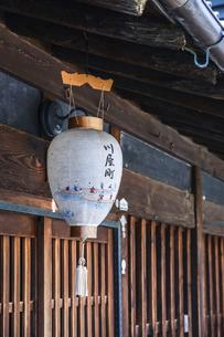 格子戸のある古い家屋の軒先に吊るされたレトロな提灯の写真素材 [FYI04731867]
