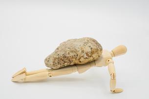 石を乗せて腕立て伏せをするストイックなデッサン人形の写真素材 [FYI04732024]