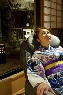 マッサージチェアに座る浴衣の女性の写真素材 [FYI04732641]