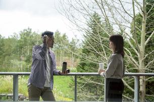 カフェのテラスで談笑する男女の写真素材 [FYI04733035]