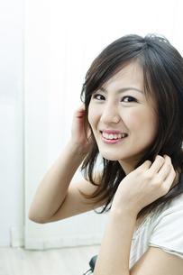 髪を触る笑顔の女性の写真素材 [FYI04733061]