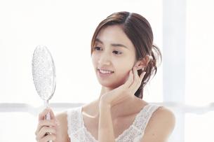 鏡を持ち頬に手をあてる若い女性の写真素材 [FYI04733645]
