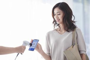 レジでスマートフォンを持ちキャッシュレス決済をする若い女性の写真素材 [FYI04733687]