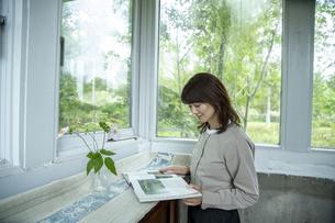 カフェギャラリーで読書する女性の写真素材 [FYI04734359]