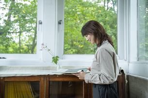 カフェギャラリーで読書する女性の写真素材 [FYI04734360]
