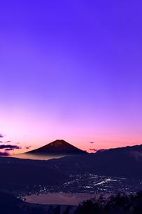 富士山を赤く染める日の出前の薄明かりと、諏訪湖面の反射と諏訪市の街灯りの写真素材 [FYI04734460]