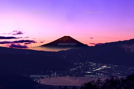 富士山を赤く染める日の出前の薄明かりと、諏訪湖面の反射と諏訪市の街灯りの写真素材 [FYI04734587]