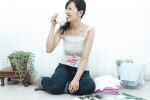 床に座ってコーヒーを飲む女性の写真素材 [FYI04735123]