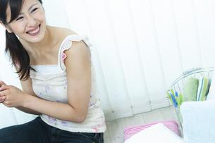 洗濯物を片付ける女性の写真素材 [FYI04735124]