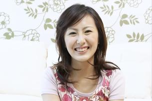 ソファーの前に座る笑顔の女性の写真素材 [FYI04735140]