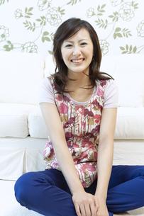 ソファーの前に座る笑顔の女性の写真素材 [FYI04735141]