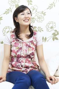 ソファーに座る笑顔の女性の写真素材 [FYI04735158]