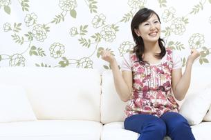 ソファーに座る笑顔の女性の写真素材 [FYI04735159]