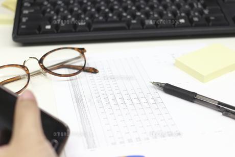 スマートフォンを持つ手と眼鏡と付箋とペンとパソコンのキーボードと書類の写真素材 [FYI04736274]