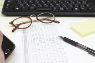 スマートフォンを持つ手と眼鏡と付箋とペンとパソコンのキーボードと書類の写真素材 [FYI04736275]