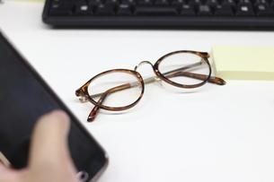 スマートフォンを持つ手と眼鏡と付箋とペンとパソコンのキーボードと書類の写真素材 [FYI04736276]