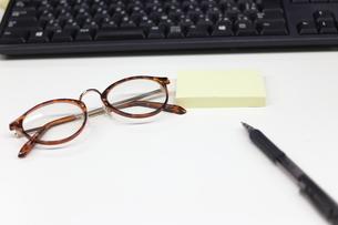 眼鏡と付箋とペンとパソコンのキーボードの写真素材 [FYI04736277]