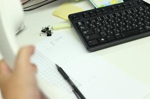 仕事用の電話を持つ手とパソコンのキーボードの写真素材 [FYI04736300]