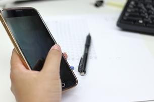 スマートフォンを持つ手とペンとパソコンのキーボードと書類の写真素材 [FYI04736302]