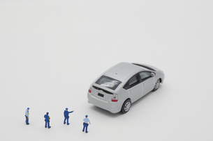 ハイブリッドカーのミニカーを指差す警察官のミニチュア人形の写真素材 [FYI04736330]