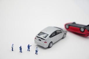事故を起こしたハイブリッドカーのミニカーを指差す警察官のミニチュア人形の写真素材 [FYI04736331]