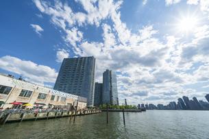 ニューヨーク市 クイーンズ ロングアイランドシティーのイーストリバー沿いのレストランと高層住宅街と対岸のマンハッタン摩天楼。の写真素材 [FYI04736760]