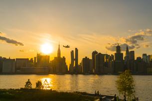 ニューヨーク市 クイーンズ ロングアイランドシティー ガントリープラザ ステイト パークの展望デッキからのミッドタウンマンハッタン摩天楼に沈む夕日。の写真素材 [FYI04736789]