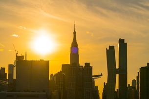 ニューヨーク市 クイーンズ ロングアイランドシティー ガントリープラザ ステイト パークの展望デッキからのミッドタウンマンハッタン摩天楼に沈む夕日。の写真素材 [FYI04736792]