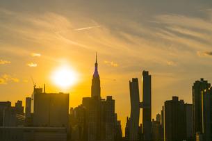 ニューヨーク市 クイーンズ ロングアイランドシティー ガントリープラザ ステイト パークの展望デッキからのミッドタウンマンハッタン摩天楼に沈む夕日。の写真素材 [FYI04736793]