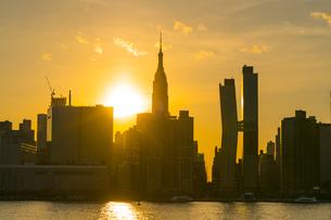 ニューヨーク市 クイーンズ ロングアイランドシティー ガントリープラザ ステイト パークの展望デッキからのミッドタウンマンハッタン摩天楼に沈む夕日。の写真素材 [FYI04736799]