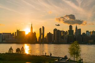 ニューヨーク市 クイーンズ ロングアイランドシティー ガントリープラザ ステイト パークの展望デッキからのミッドタウンマンハッタン摩天楼に沈む夕日。の写真素材 [FYI04736804]