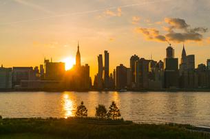ニューヨーク市 クイーンズ ロングアイランドシティー ガントリープラザ ステイト パークの展望デッキからのミッドタウンマンハッタン摩天楼に沈む夕日。の写真素材 [FYI04736806]