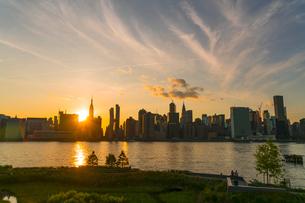 ニューヨーク市 クイーンズ ロングアイランドシティー ガントリープラザ ステイト パークの展望デッキからのミッドタウンマンハッタン摩天楼に沈む夕日。の写真素材 [FYI04736807]