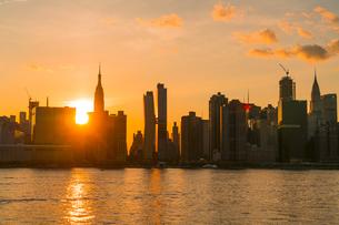 ニューヨーク市 クイーンズ ロングアイランドシティー ガントリープラザ ステイト パークの展望デッキからのミッドタウンマンハッタン摩天楼に沈む夕日。の写真素材 [FYI04736809]