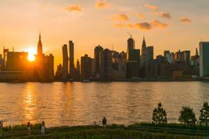 ニューヨーク市 クイーンズ ロングアイランドシティー ガントリープラザ ステイト パークの展望デッキからのミッドタウンマンハッタン摩天楼に沈む夕日。の写真素材 [FYI04736810]