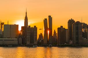 ニューヨーク市 クイーンズ ロングアイランドシティー ガントリープラザ ステイト パークの展望デッキからのミッドタウンマンハッタン摩天楼に沈む夕日。の写真素材 [FYI04736815]
