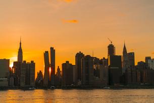 ニューヨーク市 クイーンズ ロングアイランドシティー ガントリープラザ ステイト パークの展望デッキからのミッドタウンマンハッタン摩天楼に沈む夕日。の写真素材 [FYI04736817]