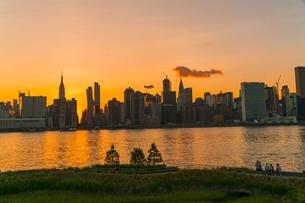 ニューヨーク市 クイーンズ ロングアイランドシティー ガントリープラザ ステイト パークの展望デッキからのミッドタウンマンハッタン摩天楼に沈む夕日。の写真素材 [FYI04736819]