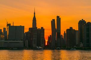 ニューヨーク市 クイーンズ ロングアイランドシティー ガントリープラザ ステイト パークの展望デッキからのミッドタウンマンハッタン摩天楼に沈む夕日。の写真素材 [FYI04736824]