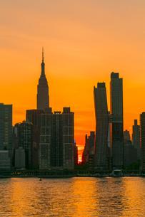 ニューヨーク市 クイーンズ ロングアイランドシティー ガントリープラザ ステイト パークの展望デッキからのミッドタウンマンハッタン摩天楼に沈む夕日。の写真素材 [FYI04736825]