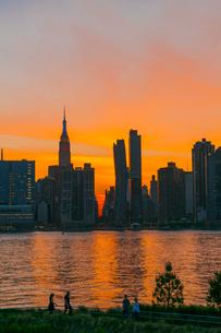 ニューヨーク市 クイーンズ ロングアイランドシティー ガントリープラザ ステイト パークの展望デッキからのミッドタウンマンハッタン摩天楼に沈む夕日。の写真素材 [FYI04736832]