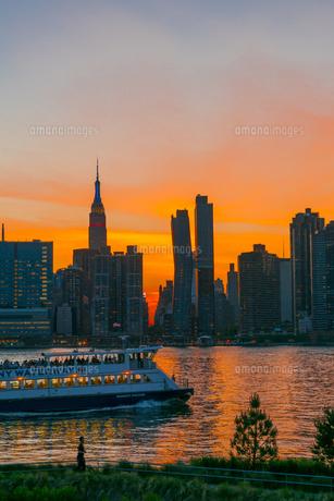 ニューヨーク市 クイーンズ ロングアイランドシティー ガントリープラザ ステイト パークの展望デッキからのミッドタウンマンハッタン摩天楼に沈む夕日。の写真素材 [FYI04736835]