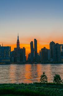 ニューヨーク市 クイーンズ ロングアイランドシティー ガントリープラザ ステイト パークの展望デッキからのミッドタウンマンハッタン摩天楼に沈む夕日。の写真素材 [FYI04736839]