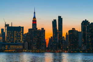 ニューヨーク市 クイーンズ ロングアイランドシティー ガントリープラザ ステイト パークの展望デッキからのミッドタウンマンハッタン摩天楼に沈む夕日。の写真素材 [FYI04736842]