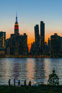 ニューヨーク市 クイーンズ ロングアイランドシティー ガントリープラザ ステイト パークの展望デッキからのミッドタウンマンハッタン摩天楼に沈む夕日。の写真素材 [FYI04736843]