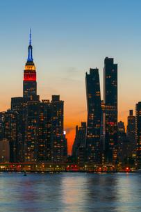 ニューヨーク市 クイーンズ ロングアイランドシティー ガントリープラザ ステイト パークの展望デッキからのミッドタウンマンハッタン摩天楼に沈む夕日。の写真素材 [FYI04736847]
