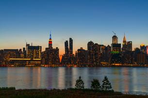 ニューヨーク市 クイーンズ ロングアイランドシティー ガントリープラザ ステイト パークの展望デッキからのミッドタウンマンハッタン摩天楼に沈む夕日。の写真素材 [FYI04736848]