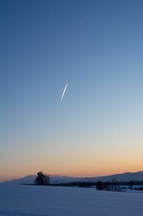 冬の夕暮れの空と飛行機雲の写真素材 [FYI04737165]