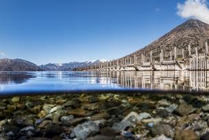 中禅寺湖の崩れかけた桟橋と水中の半水面風景の写真素材 [FYI04737351]